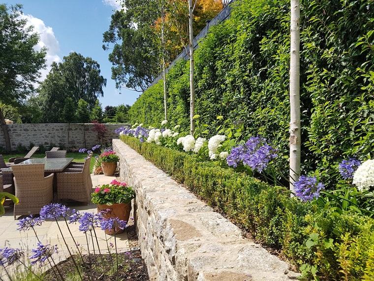Arredo giardino con mobili in rattan e un tavolo, muro in pietra e siepe molto alta
