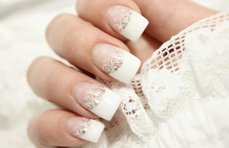 Unghie belle, french manicure donna con decorazioni effetto pizzo e piccoli brillantini