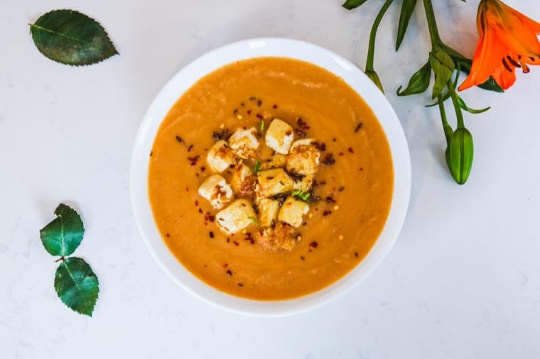 minestra di zucca con dei cubetti di tofu saltato e semi di sesamo tostati