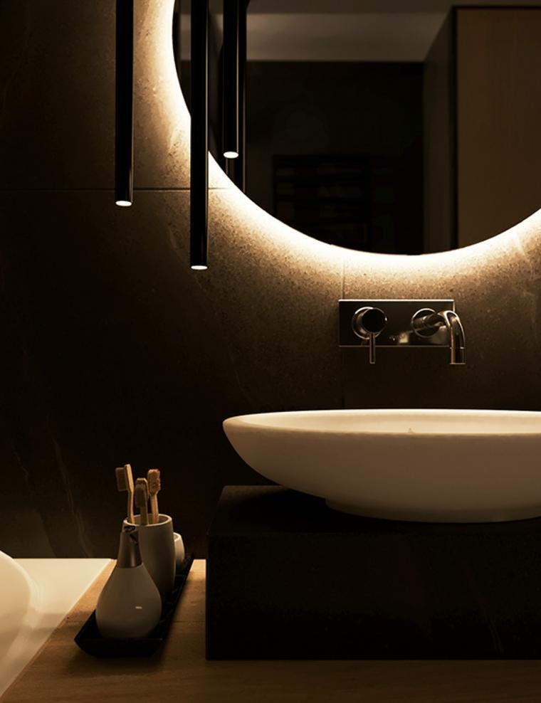 Bagno con lavandino da appoggio forma ovale e rubinetto da parete, specchio con retroilluminazione e lampade sospese