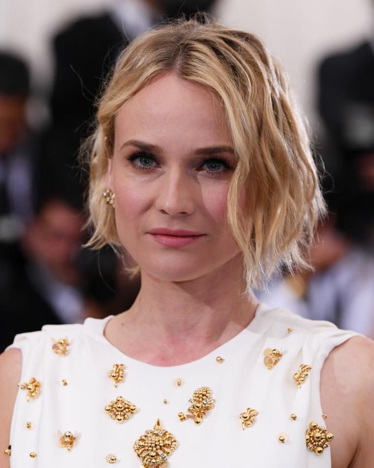 Taglio capelli corti di colore biondo effetto mosso, abbinamento ad un vestito bianco con gioielli