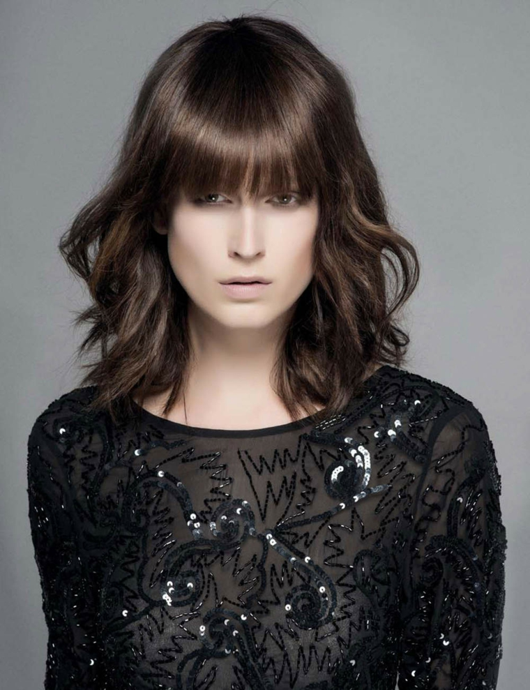 Taglio capelli lunghi con frangia e ricci sulle lunghezze, colorazione castano scuro