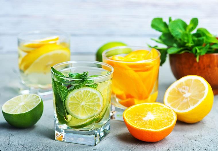 Bicchieri di vetro con acqua aromatizzata agli agrumi e foglie di menta