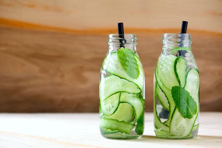 Due bottiglie di vetro con acqua aromatizzata al cetriolo e spezie