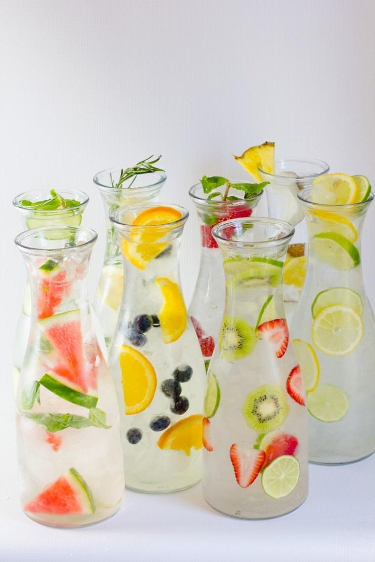 Bevande detox fai da te, caraffe di vetro con acqua e tanta frutta tagliata a pezzettini