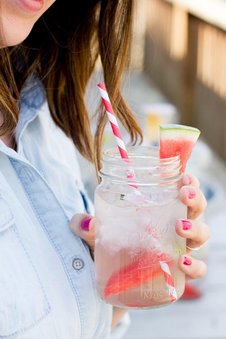 Idea per bevande detox a base di acqua e pezzettini di anguria, donna che beve da un barattolo con cannuccia