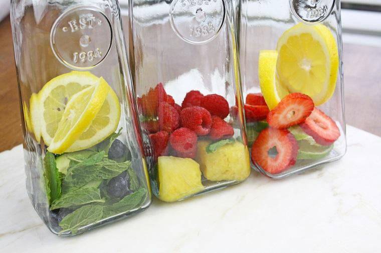 Tre caraffe di vetro con frutta, abbinamento di lamponi con ananas e foglie di menta