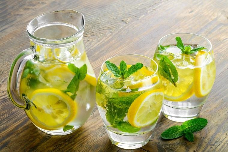 Due bicchieri di vetro con acqua aromatizzata al limone e menta