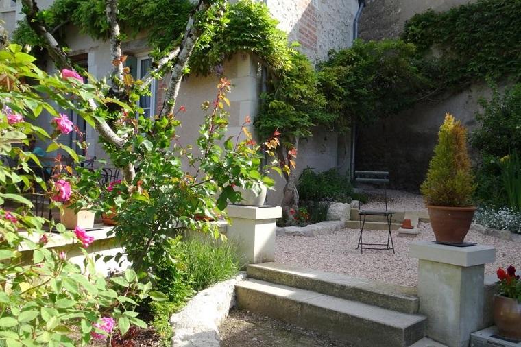Pavimentazione giardino con ghiaia, tante piante da giardino fiorite e alberi