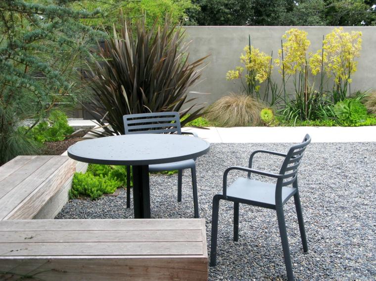 Arredamento di un giardino piccolo con un tavolo rotondo e una panchina di legno