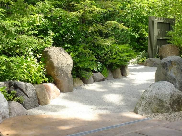 Camminamento di un giardino con ghiaia e grandi rocce intorno, tante piante sempreverdi