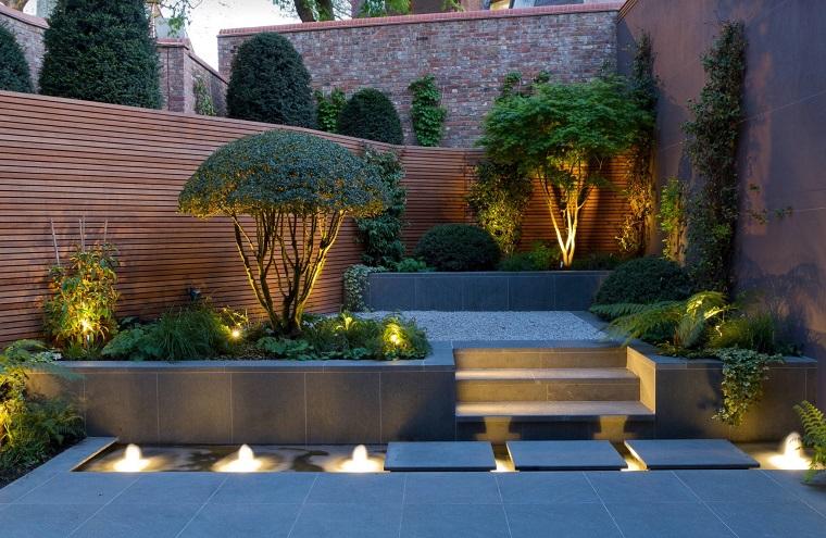 Piante ornamentali da giardino, recinzione in legno e piccole fontane illuminare