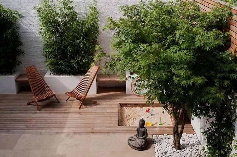 Idea per piccoli giardini con pavimento in legno e zona di gioco con sabbia
