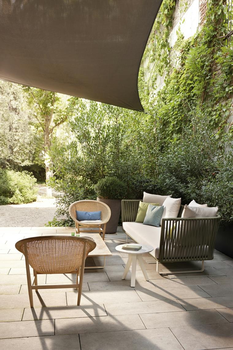 Alberi sempreverdi in un giardino piccolo, arredamento con mobili in rattan sintetico