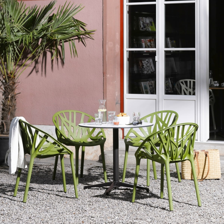 Piante da giardino sempreverdi, arredamento con un tavolo rotondo e quattro sedie di colore verde in plastica