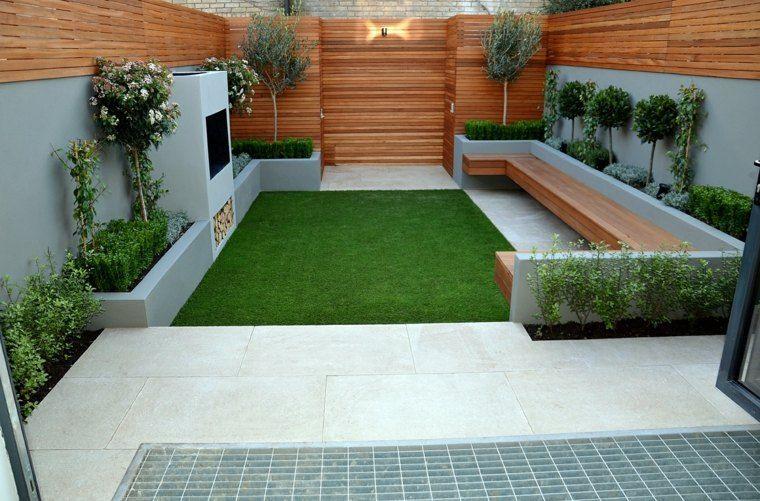 Piccoli giardini con erba e piante sempreverdi, camino da esterno a legna e una panchina in legno