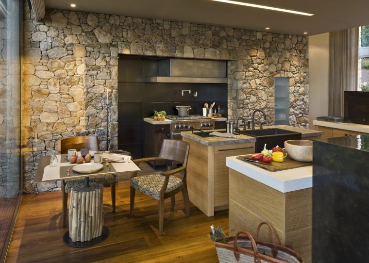 cucina rustica con piccola isola attrezzata, piccolo tavolo e rivestimento parete in pietra