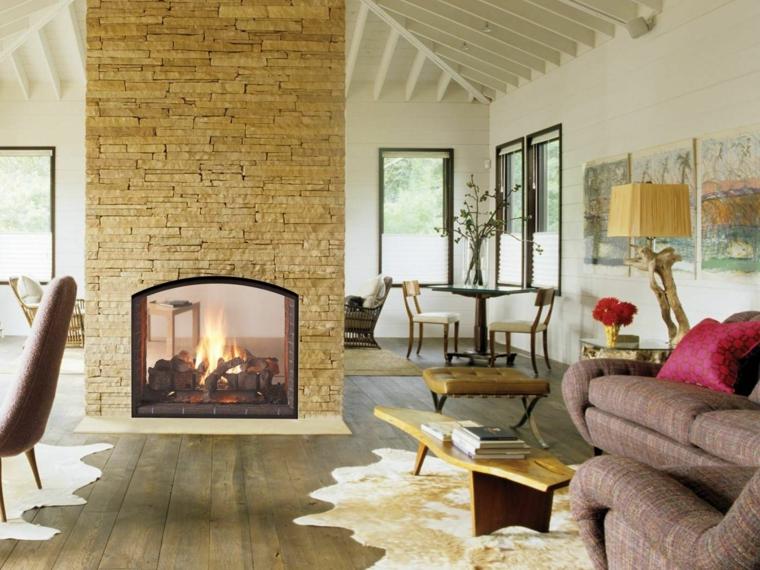 accogliente salotto con poltrone viola melange, tappeto, tavolino basso in legno e camino in pietra
