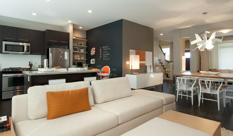 arredare open space cucina soggiorno idee con mobili della cucina neri, divano bianco, tavolo da pranzo e da caffè in legno chiaro