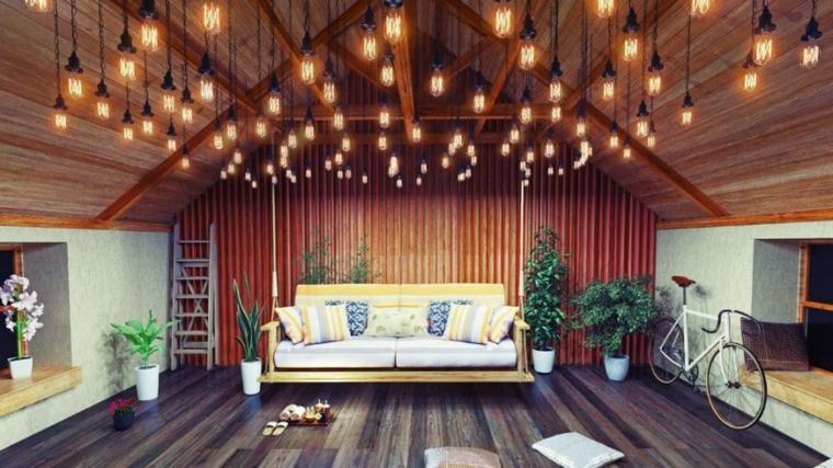 suggestiva mansarda arredata con un divano lineare, tante luci appese al soffitto, piante e bicicletta