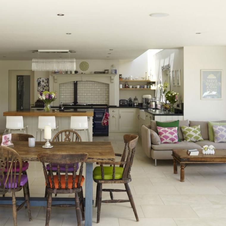stile country cucina open space con tavolo e sedie in legno con cuscini colorati, divano grigio