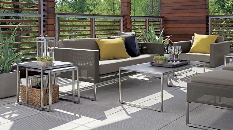 Piccoli giardini e un arredamento con mobili in metallo di colore grigio, decorazione con cuscini gialli e piante in vasi