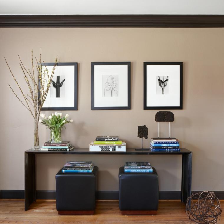 stile essenziale per l'arredamento di una parete con tavolo e puff neri, esempio di abbinamento color tortora