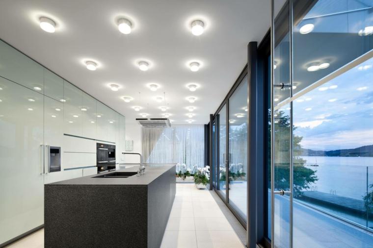 open space dallo stile moderno ed essenziale con una grande isola cucina nera con lavello e piano lavoro