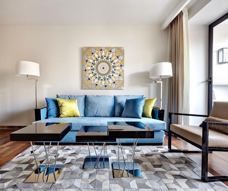 Divano di colore blu e tavolini lucidi in un piccolo soggiorno con grande finestra