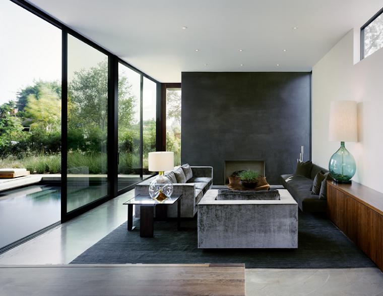Arredamento salotto moderno con un divano velvet di colore grigio, parete nera con una nicchia