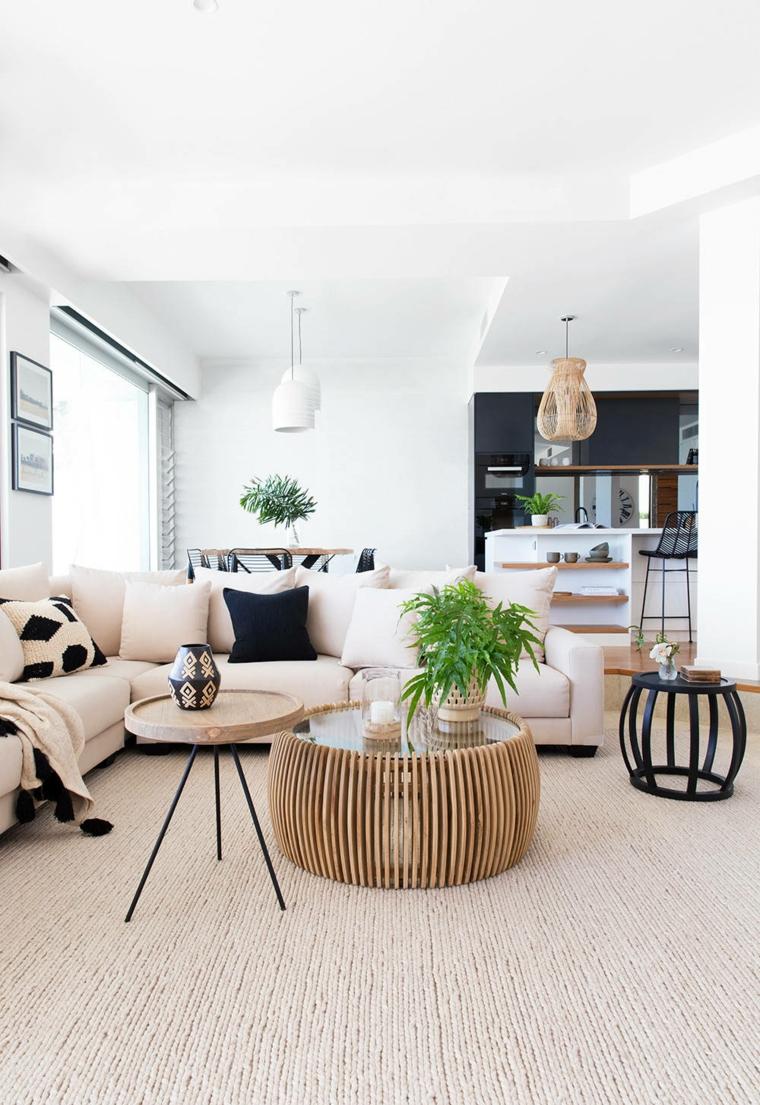 Open space cucina soggiorno con un divano angolare e tavolini rotondo con vasi
