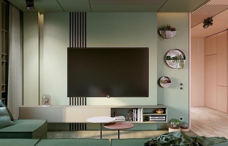 Parete attrezzata moderna con mobili di colore bianco sospesi, arredamento soggiorno con divano verde e tavolini