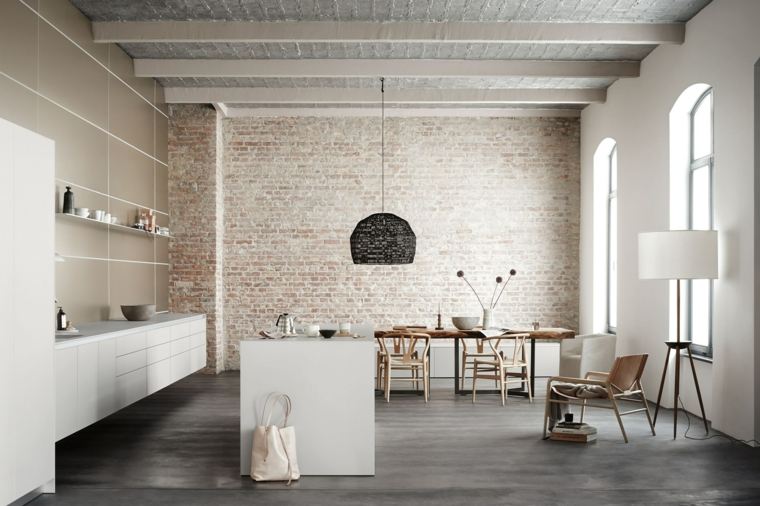 parete con mattoni a vista mobili della cucina bianchi lineari e lampadario a sospensione nero