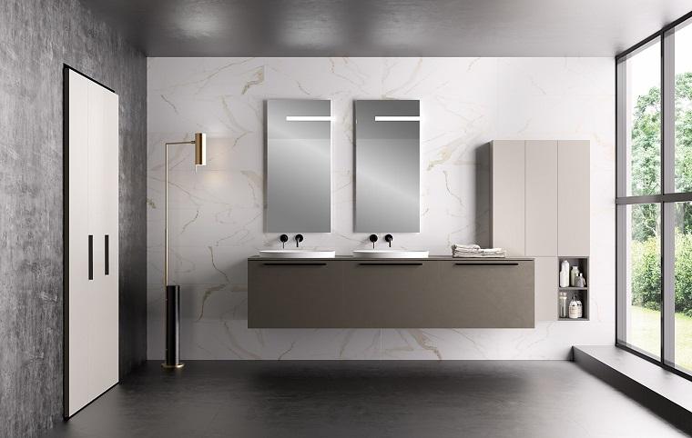 Sala da bagno arredata con un mobile sospeso e due lavabi, lampada da terra metallo color oro