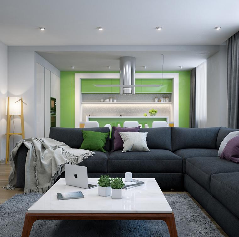 Open space cucina soggiorno con un divano angolare di colore grigio scuro e tavolino bianco quadrato