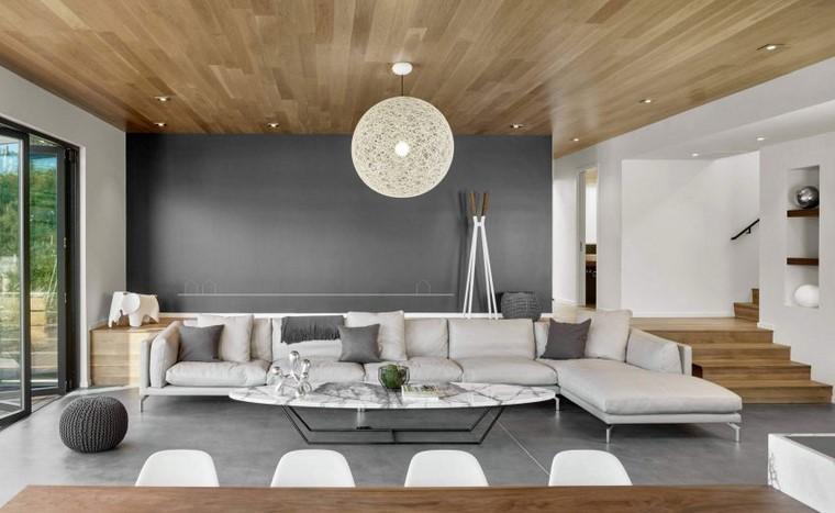 Idee arredo casa e un soggiorno con divano grigio e penisola, tavolo con superficie effetto marmo