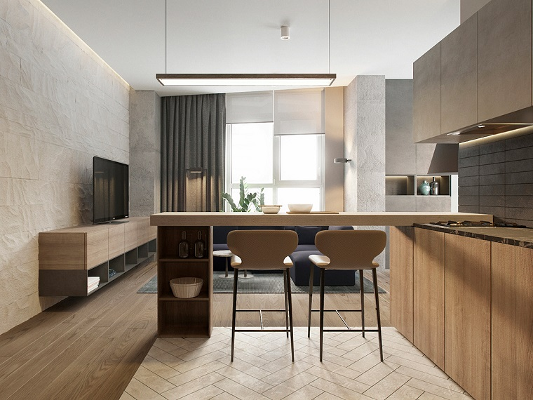 Open space cucina soggiorno con isola e sgabelli alti, pavimento in legno con tappeti colorati