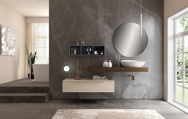Sala da bagno con parete rivestita con microcementizio colore grigio, mobili di legno e lavabo da appoggio