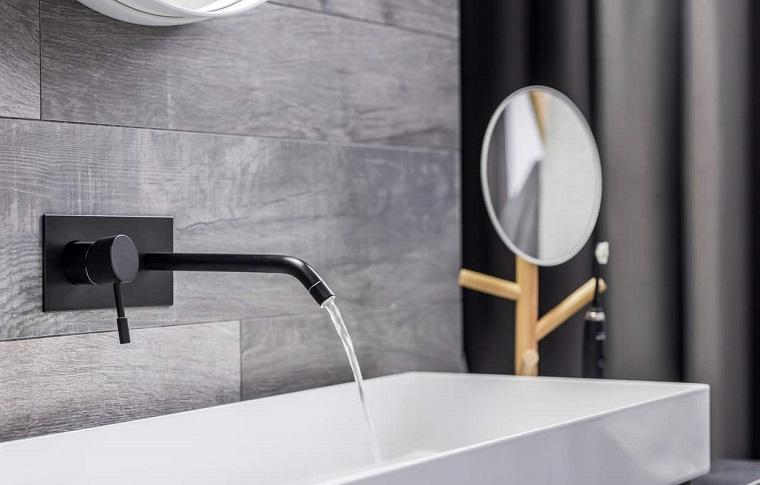 Rubinetto di colore nero per un bagno rivestito con piastrelle effetto legno