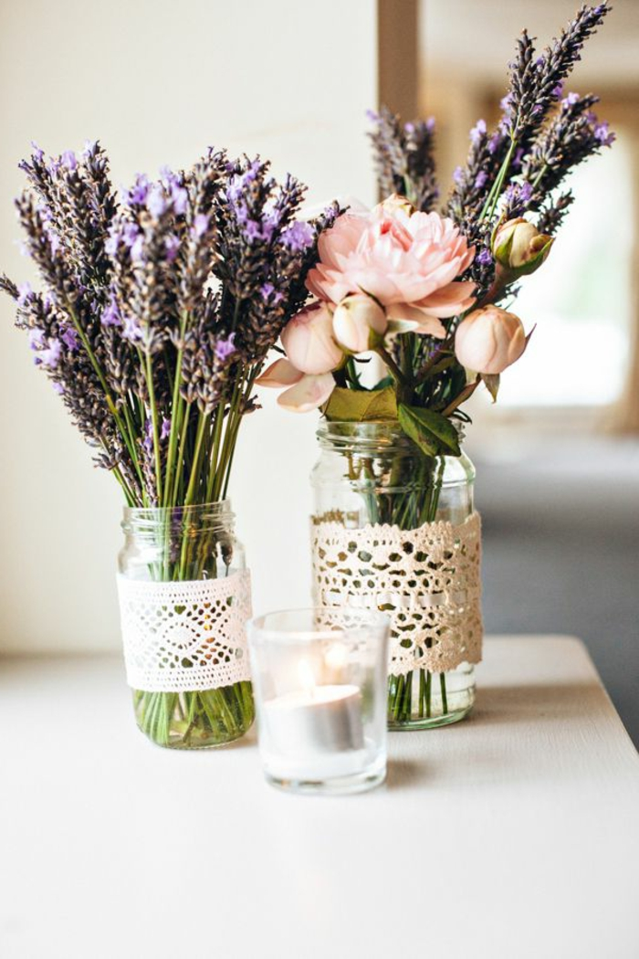 Centrotavola con dei barattoli di vetro utilizzati come vasi per dei fiori di lavanda