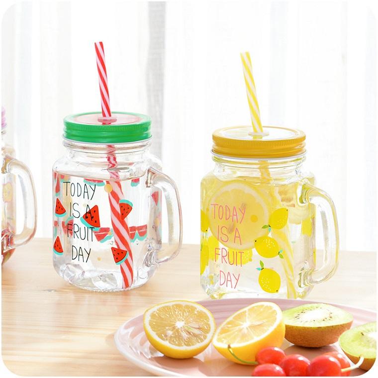 Acqua aromatizzata alla frutta da servire in barattoli di vetro e bere con cannucce