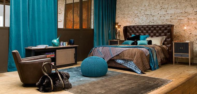 originale camera da letto con struttura del letto marrone, tende turchesi, poltrona marrone e parete rivestita in pietra