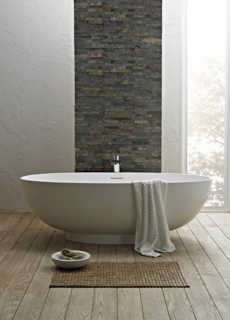 bagno moderno con vasca ovale bianca, asciugamano bianco, tappeto piccolo e parete in pietra