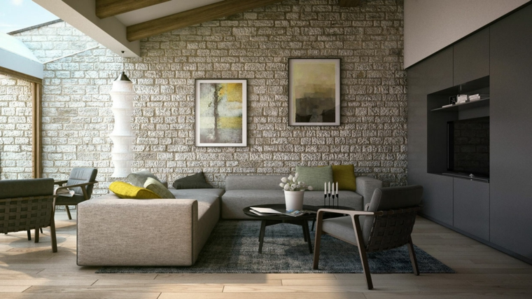 salotto in mansarda arredato con divani e poltrone grigie, tappeto grigio, quadri e pareti rivestite in pietra