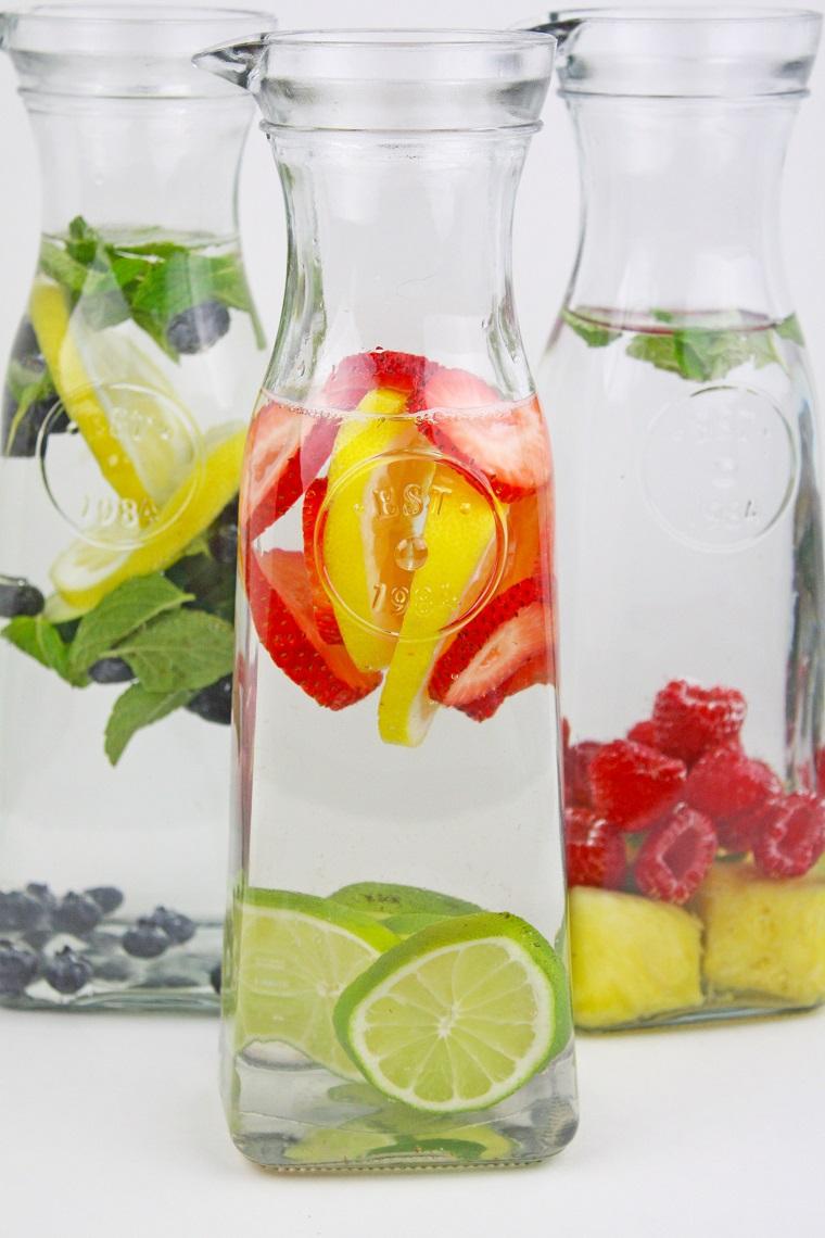 Acqua detox ricette, tre caraffe di vetro con frutta e foglie di menta