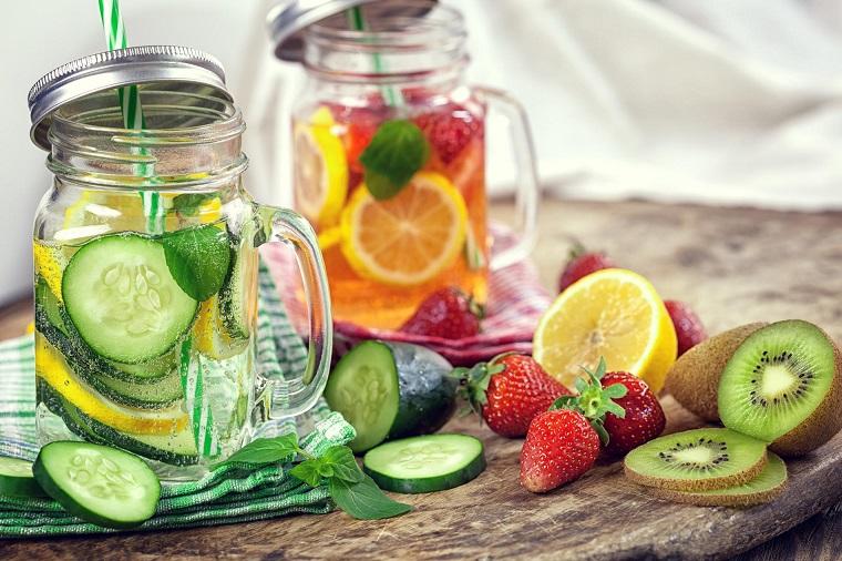 Frutta tagliata a pezzettini su un tavolo di legno, acqua aromatizzata detox in barattoli di vetro