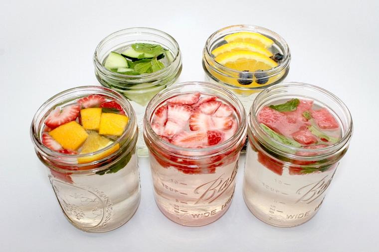 Acqua detox servita in barattoli di vetro, frutta tagliata a pezzettini in abbinamento con delle foglie di menta