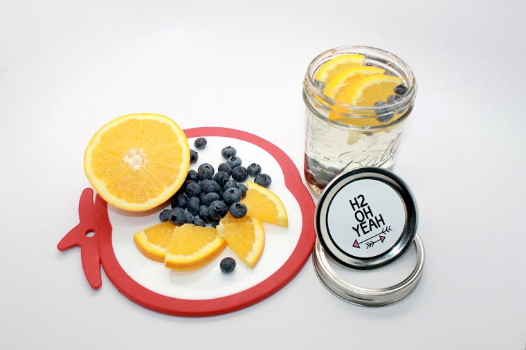 Bevanda sgonfia pancia a base di acqua, mirtilli e pezzettini di limone, servita in barattolo di vetro
