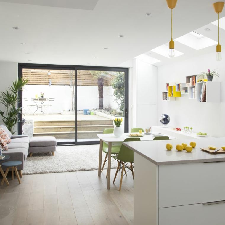 come arredare open space cucina soggiorno con mobili della cucina bianchi, tavolo per quattro con sedie verdi e divano grigio