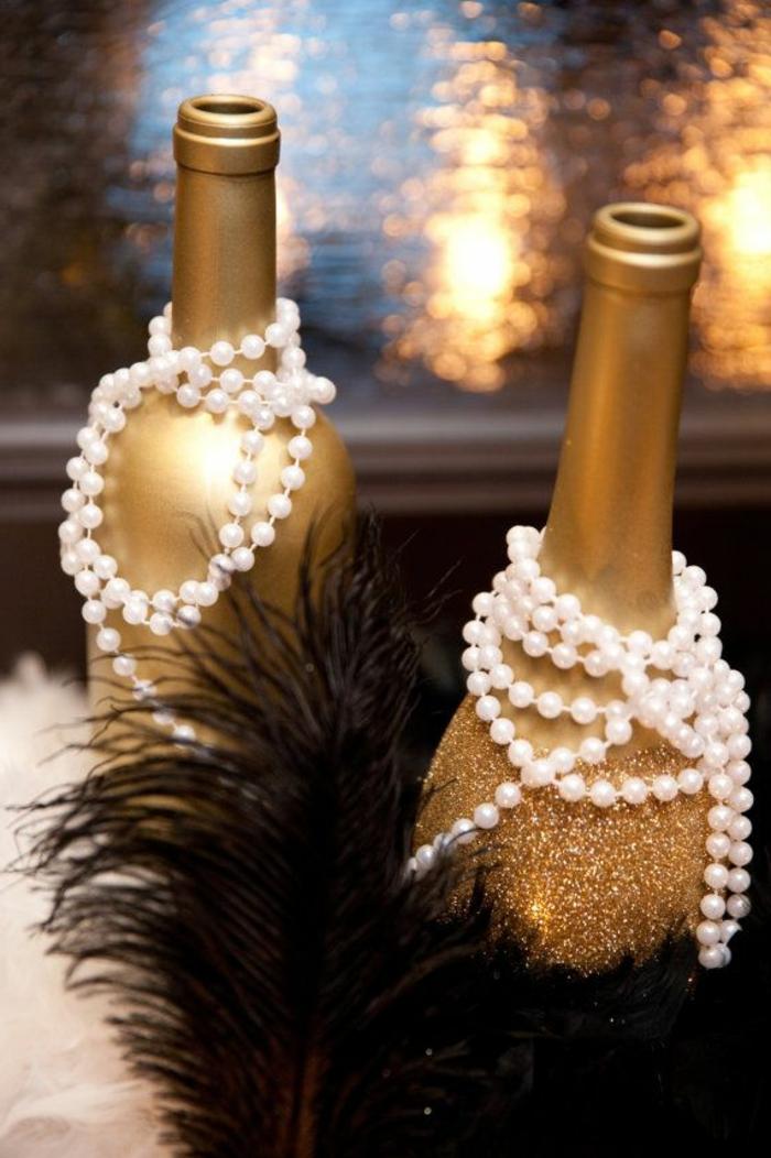 Tavole natalizie, bottiglie di champagne, collane con perle, piume colore nero